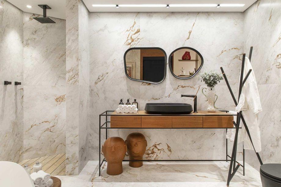 <span>Sala de Banho - Fabíola e Eliana Caramuru. Em Ribeirão Preto, o espaço destaca o porcelanato com aparência de mármore, que alia delicadeza e robustez. O cabideiro, os metais, a moldura dos espelhos e o mobiliário brasileiro criam linhas de força visuais.</span>