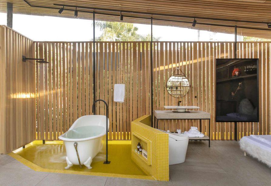 Loft DECA - Mariana Orsi. CASACOR Ribeirão Preto 2019. O espaço integrado de 56 m² se abre para o jardim através do vidro e da permeabilidade do painel em madeiraTauari maciça. No banheiro, uma proposta de layout solto e desregrado é complementada pelo ladrilho hidráulico amarelo.