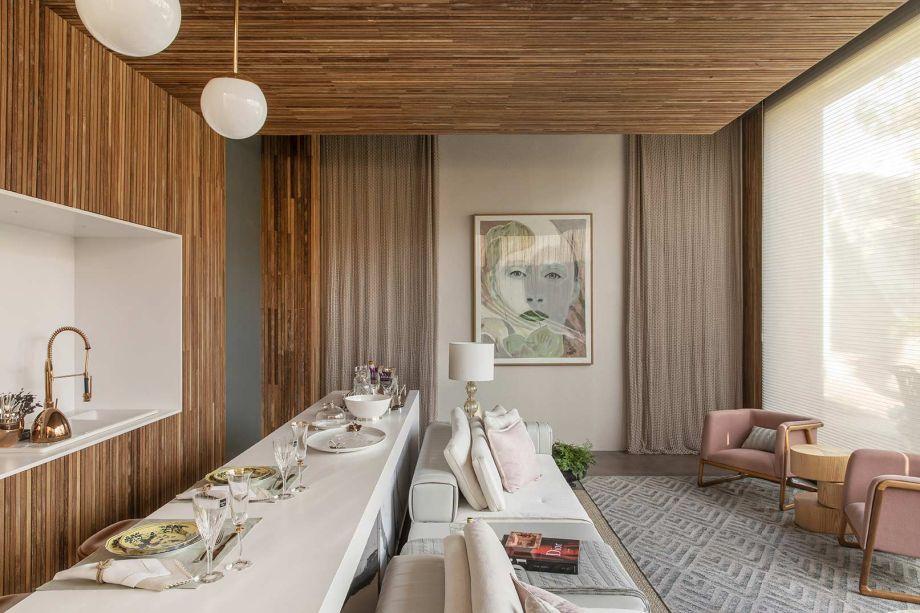 O espaço conta ainda com jantar, que se desenha em torno da celebração do receber. O teto de madeira alcança a parede da cozinha, que se encerra com uma pia encaixada em um nicho.