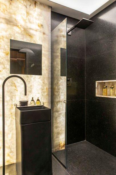 Juliana Said - Banheiro da Maioridade. Os 4 m² bastaram para criar um espaço para relaxar. Inesperada, a escolha do granito escuro se torna equilibrada quando interage com a parede retroiluminada em ônix branco. No teto, o forro foi substituído por uma tela tensionada para potencializar a iluminação.