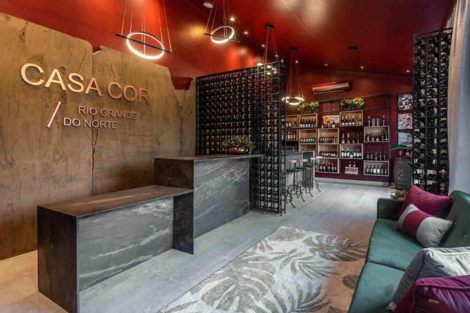 Lorena Azevedo - Lounge da Recepção. O espaço une a bilheteria e uma loja de vinhos, utilizado com funcionalidade e valorizado pela mistura de materiais. As cores escolhidas foram inspiradas nas uvas e nas folhas verdes das parreiras. A pedra utilizada nas paredes e no balcão de atendimento trouxe a tonalidade do marrom que remete aos caules.
