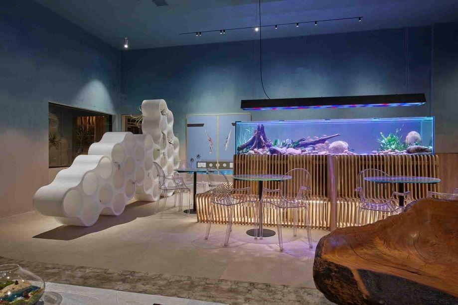 Elder Galvão - Lounge AVIVA. Água, mar e natureza são as inspirações para a concepção do espaço de 90m². O ambiente explora a beleza e a simplicidade com sofisticação. O mobiliário, desenvolvido por grandes designers internacionais, como Philippe Starck, é transparente, imprimindo leveza em contraste com as o colorido das paredes e da iluminação.Um aquário de três metros de comprimento é o grande protagonista do ambiente. Obras de artes de artistas nacionais, como Sonia Menna Barreto, e quadros metacrilato do fotógrafo Bento Viana completam a composição.