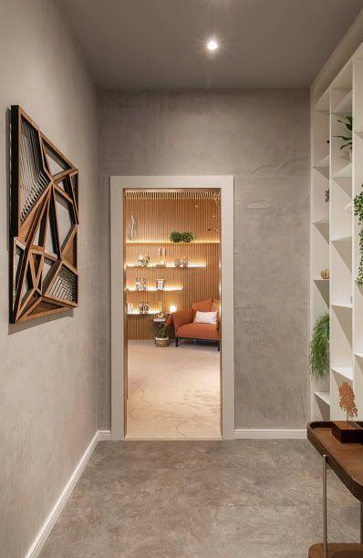 Hall das Lojas - Kamila Torres. O espaço de 4,74 m² conecta os ambientes residenciais e as lojas da mostra. Por isso, tem como proposta ser delicado e acolhedor, envolvendo as pessoas que transitam. O piso laminado com aparência de concreto teve aplicação rápida, a partir do encaixe das peças.