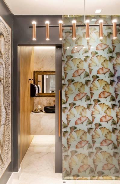 Lavabos Unissex - Janete Valladão. O espaço de 10 m² exibe iluminação moderna, uma parede com print floral protegida pelo vidro e um porcelanato que reproduz o mármore da região italiana de Sorrento no piso.