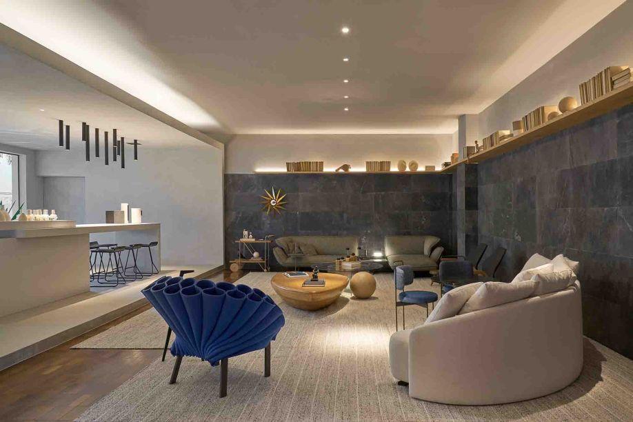 CASACOR Brasília 2019. Lounge PS - Studio Arch +. Com referências na arquitetura minimalista, o ambiente de 120 m² se define pelas formas puras e retas. Algumas peças do mobiliário quebram a austeridade das linhas, como os sofás de formato orgânico e a divertida poltrona Peacock na cor azul, do designer Dror Benshetrit para a Cappellini. (Teto e paredes: Tubarão Branco (cinza)