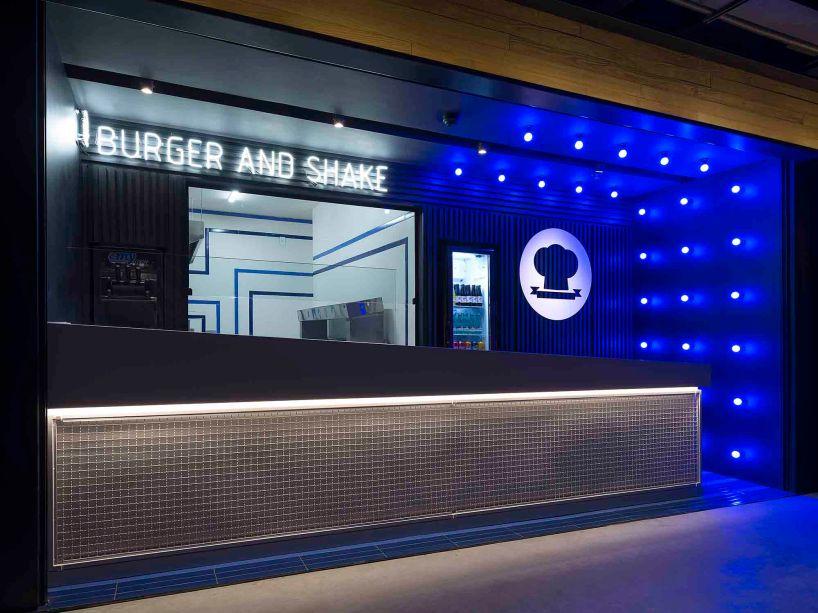 Burger Dream - 3P Studio. Com uma fachada única, o projeto enaltece as linhas retas, o gradil, o P&B e a cor azul da primeira sede do restaurante. Painéis ripados na cor preta emolduram e destacam a grande vitrine para a cozinha, na qual o movimento das linhas azuis quebram a formalidade dos volumes brancos. Repare que o grande balcão em Silestone foi instalado na diagonal para, mais uma vez, criar movimento e refletir já no primeiro momento o dinamismo da operação.
