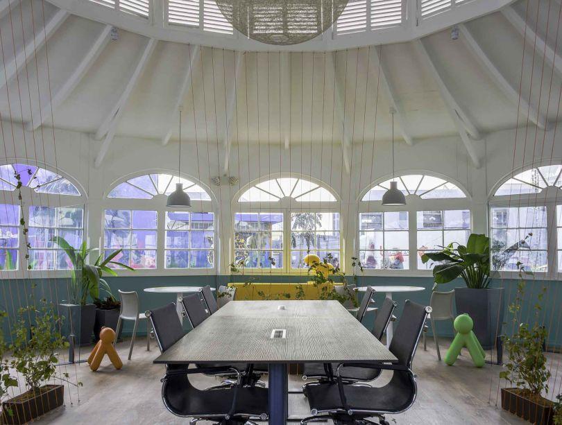 """Worx Coworking - Anda Rajkovic e Giancarlo Chacaliaza. A arquitetura original é plenamente aproveitada, com dimensões que permitem o uso colaborativo do espaço. Para delimitar áreas de trabalho, fios na cor laranja são tensionados até o teto e desenham delicadas estruturas flexíveis. """"Decidimos usar cores e materiais vivos, quentes, além de vegetação e luz natural. Eles nos inspiram a ser mais produtivos e sensíveis ao nosso planeta"""", comenta a dupla."""