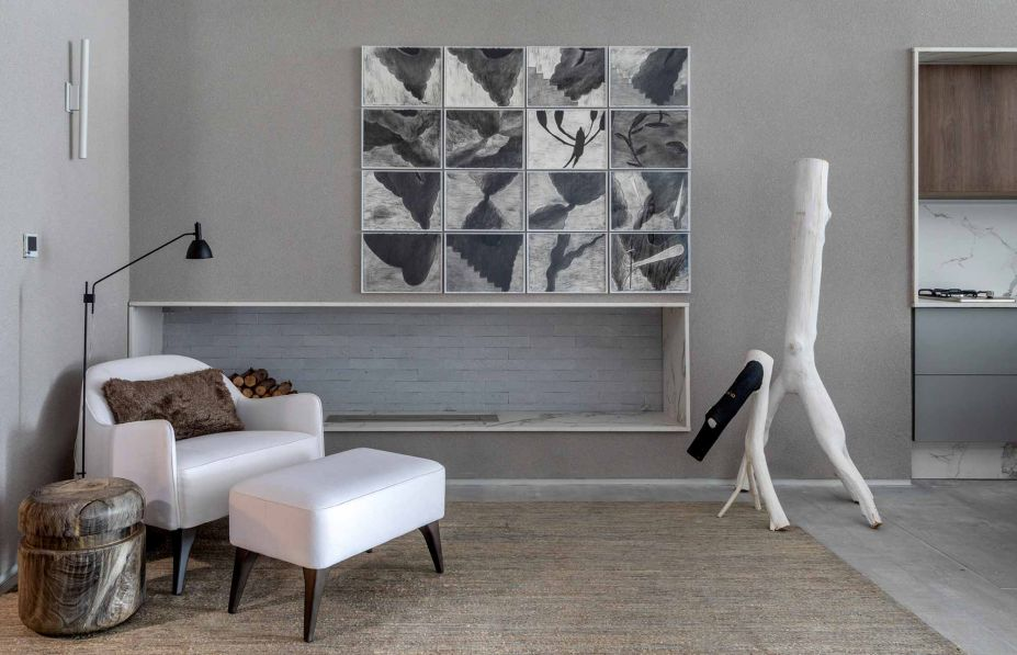 A Casa DOA de Jacira Pinheiro conta com um minimalismo estrutural, de poucos objetos e pouco mobiliário, que contribuem para ressaltar o essencial: as artes, como a escultura de Véio em destaque no living.
