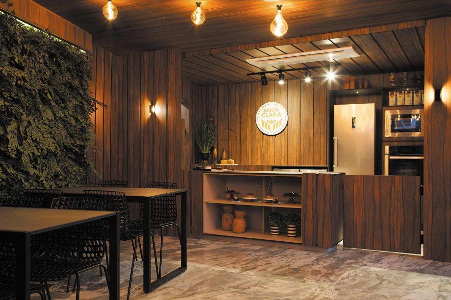 O Café Santa Clara, da arquiteta Sandra Bione, traz a madeira por toda parte, em um espaço agradável que permite a degustação ou boas conversas. Integrado com a natureza, os 40m² trazem uma estética natural no salão da área de atendimento, que recepciona os clientes com a suavidade do tom rosado e as nuances de bege. Os tampos da mesa foram revestidos em couro, Usado na criação dos painéis e móveis, em harmonia com os tons do ambiente.