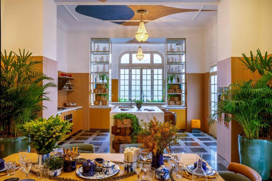 O arquiteto Jean de Just convidou a artista Naiara Bandoli para decorar o teto do ambiente Além da Cozinha. O espaço, que reúne sala de jantar, cozinha e área de serviço ganhou mais vida em meio à composição de cores quentes, como o mostarda nas paredes e as lâminas de carvalho. Verde e azul marinho estão nos detalhes.