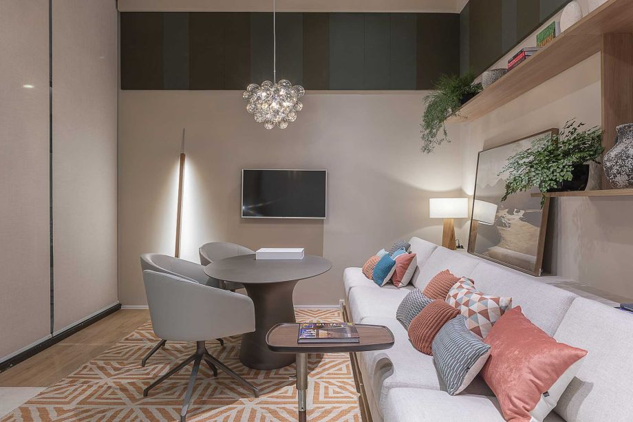 A sala multifuncional assinada por Athié Wohnrath destaca um grande sofá planejado que orienta o layout. Diferentes tonalidades de azul garantem uma descontração ao ponto de encontro, reforçada pelo tapete geométrico coral e pela composição não simétrica das prateleiras.