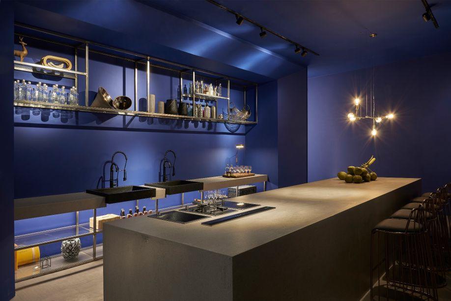 Cine Gourmet - CLX - Miguel Gustavo. Moderno e com iluminação marcante, o ambiente conta com um enorme telão que reproduz filmes e programas de televisão. Com 129 m², os revestimentos em madeira predominam, ao lado do azul profundo que colore a cozinha gourmet.