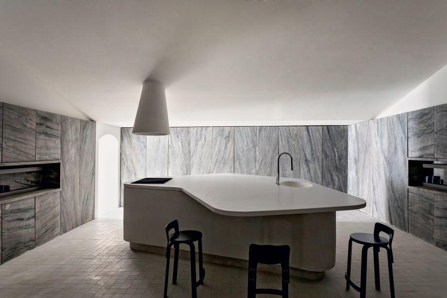 Cucina Pietra - Felipe Hess. Em sua estreia em CASACOR, o profissional aposta no minimalismo, aliado à tecnologia e precisão do mobiliário presente no ambiente. Com revestimento de pedra, os armários se fundem com as paredes, compondo um espaço absolutamente sofisticado e atemporal.