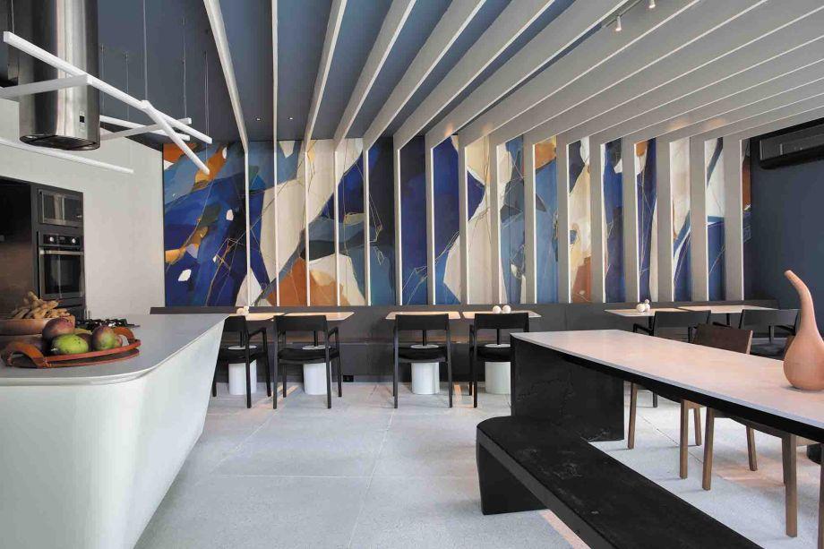 Copergás Gourmet - PORTONEVES Arquitetura. Os olhares logo se voltam para a arte atribuída à parede principal, que reúne diferentes tonalidades de azul reveladas por pergolado vertical que se estende por todo o teto. Em diálogo entre arte e design, o espaço foi concebido para receber os visitantes com a sofisticação do mobiliário contemporâneo.