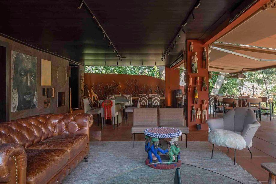 Flávio Bahia e Will Lobato - Restaurante. Com uma pegada africana, o restaurante utiliza madeira escura nas paredes e no teto, além de rolôs na cor café. No piso, a cerâmica lembra o aço corten e se integra à paleta, que inicia com os terrosos e alcança o cobre. Ao fundo, as mesas com formatos variados são acompanhadas de cadeiras estofadas em linhão, algumas com plotagem de figuras africanas no tecido. Em primeiro plano, o lounge mescla o estilo inglês, com sofá Chesterfield em tom café, móveis da década de 1940 e a mesa em ráfia, de Elisa Atheniense.