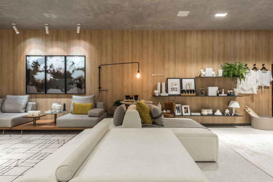 O amadeirado aparece no loft como a textura favorita, aparecendo como revestimento da maior parede do ambiente. Um grande sofá modular divide o quarto com a prateleira suspensa, que confere geometria à decoração.