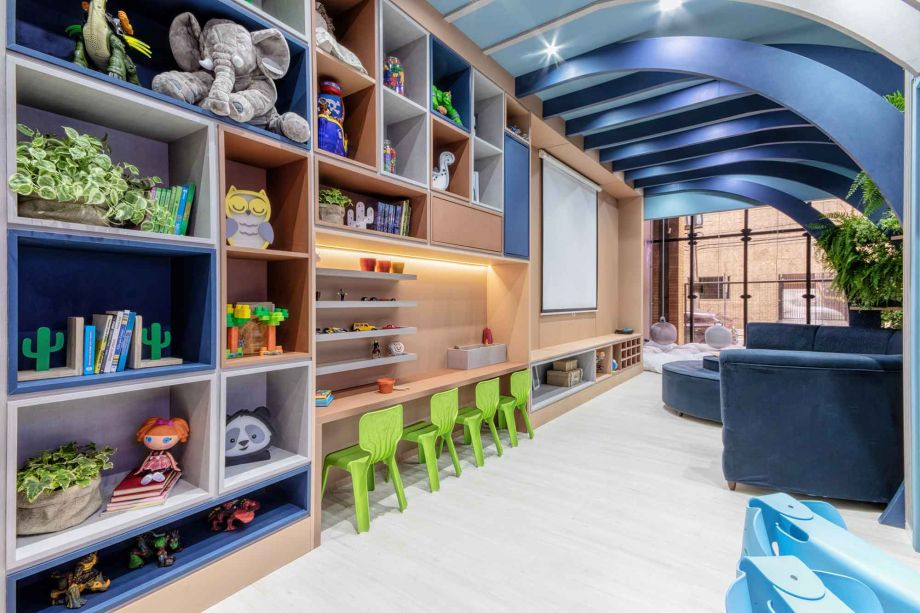 Gabriela Meister e Roseli Aderno levam ao Paraná uma proposta de inovação pelas cores. Cinza, azul, terracota e grafite aparecem na marcenaria da Brinquedoteca de 44 m² em vez de cores primárias. Pérgolas em forma de cúpula e almofadas de nuvens criam um refúgio lúdico e criativo, com inspiração no espaço sideral.