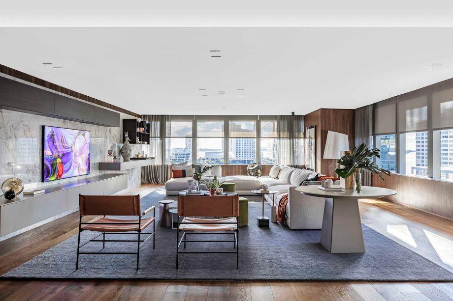 """Family Room - Allan Malouf. O quarto elegante representa uma grande mudança em relação ao seu projeto de 2018 para a CASACOR Miami. """"No ano passado, criamos um espaço muito colorido """", diz Malouf. """"Nosso projeto nesta temporada é sobre uma paleta de cores neutras. Os tons esbranquiçados, cinza claro e noz quente criam uma atmosfera acolhedora e sofisticada. O grande sofá em forma de L, bem no centro da sala, pode acomodar a família e convidados confortavelmente. Como uma lembrança de suas origens brasileiras, o designer de interiores selecionou materiais naturais da América do Sul. Eles aparecem no piso de madeira e nas estantes, bem como na pedra de mármore que emoldura a TV."""