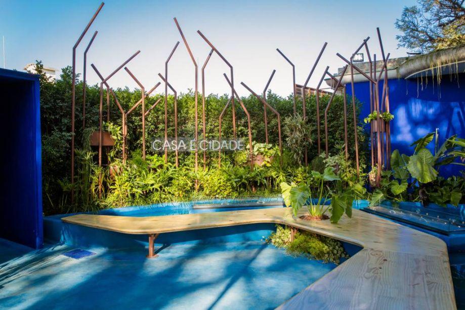 """Espaço Índigo Comgás - Lao Design e Zoom Urbanismo, Arquitetura e Design. O Zoom Arquitetura, em parceria com a LAO Engenharia, desenvolveu o """"Espaço Índigo Comgás"""" - um jardim interativo, localizado na entrada da mostra. O projeto destaca soluções sustentáveis, como o reaproveitamento de materiais, piso drenante, uma floresta de dutos metálicos reciclados e bancos em madeira de produção sustentável. Destaque para o Tubo de Rubens, um experimento físico em que chamas de fogo dançam ao ritmo de ondas sonoras musicais, o banco Marquise - referência a Oscar Niemeyer e o Bicicletário Mandacaru, uma homenagem a Lina Bo Bardi e incentivo aos visitantes para que façam uso de modais ativos."""