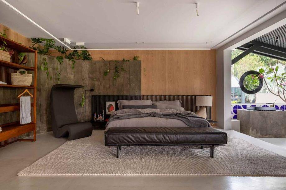 O grande painel de concreto e madeira une os ambientes de sala de estar e quarto, proporcionando uma sensação de continuidade visual. Ao lado, um banheiro é avivado por azulejos azuis, também em referência ao modernismo brasileiro.