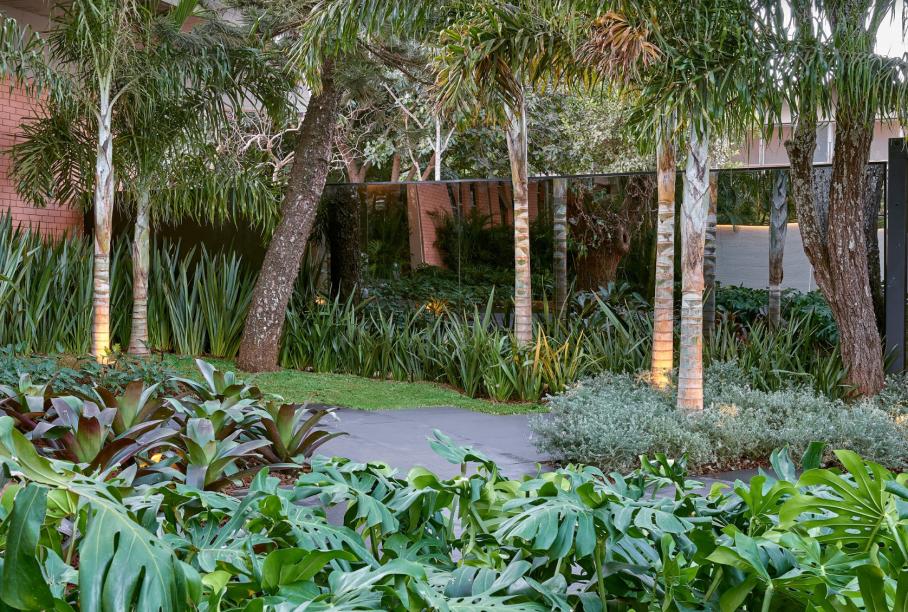 CASACOR Brasília 2019. Marina Pimentel, Eduardo Sainz e Lilian Glayna Sainz - Pavilhão São Geraldo. O espaço de 680 m² conecta a natureza com o urbano, ao mesclar a arquitetura de linhas retas da Sainz com a vegetação densa do paisagismo de Marina Pimentel. A ideia foi criar um percurso quase labiríntico e bancos soltos. Eles reduzem o ritmo da caminhada e do olhar para contemplar as folhas largas, a leveza dos bambus, os enormes Flamboyants existentes. Os caminhos geométricos foram revestidos em porcelanato escuro, exatamente pata contrastar com o verde intenso.