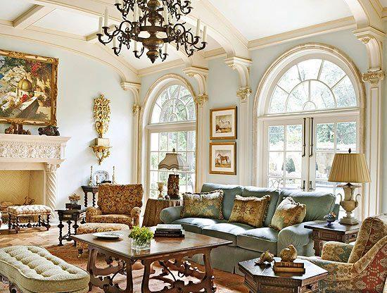 Sala com decoração vitoriana. Lustre, pinturas nas paredes. Sofás e muitas almofadas. Janelas em forma de arcos. Mesa de centro em madeira