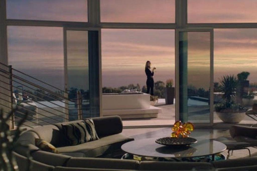 Apartamento com grande janela e varanda. Mesa e sofá em primeiro plano. Varanda com mulher ao fundo