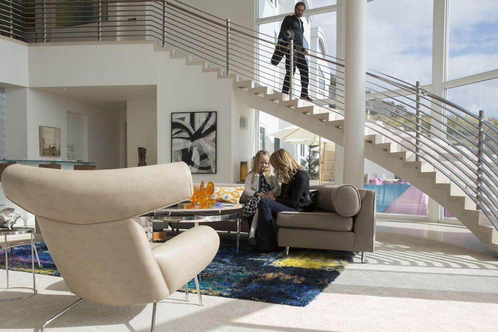 Apartamento com piso e paredes brancas. Sofás e poltronas no centro. Uma escala curva conecta primeiro e segundo andar