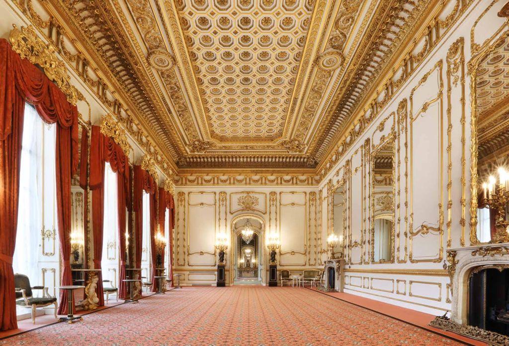 Interior de sala de palácio com tapete vermelho, teto e paredes ornamentadas com detalhes dourados. Janelas altas com cortinas vermelhas