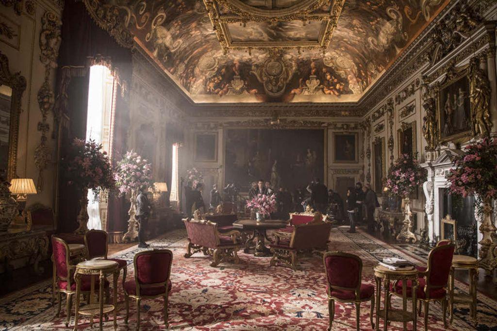 Sala de palácio com tapete vermelho ornamentado. Tero com afrescos. Pinturas nas paredes. Cadeiras e poltronas vermelhas