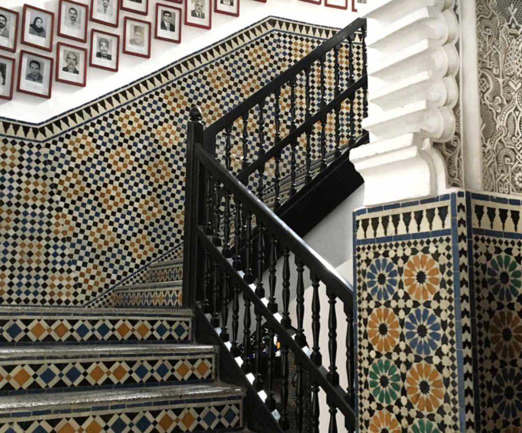 Escadaria coberta com ladrilhos azuis, verdes e amarelos, compondo padrão