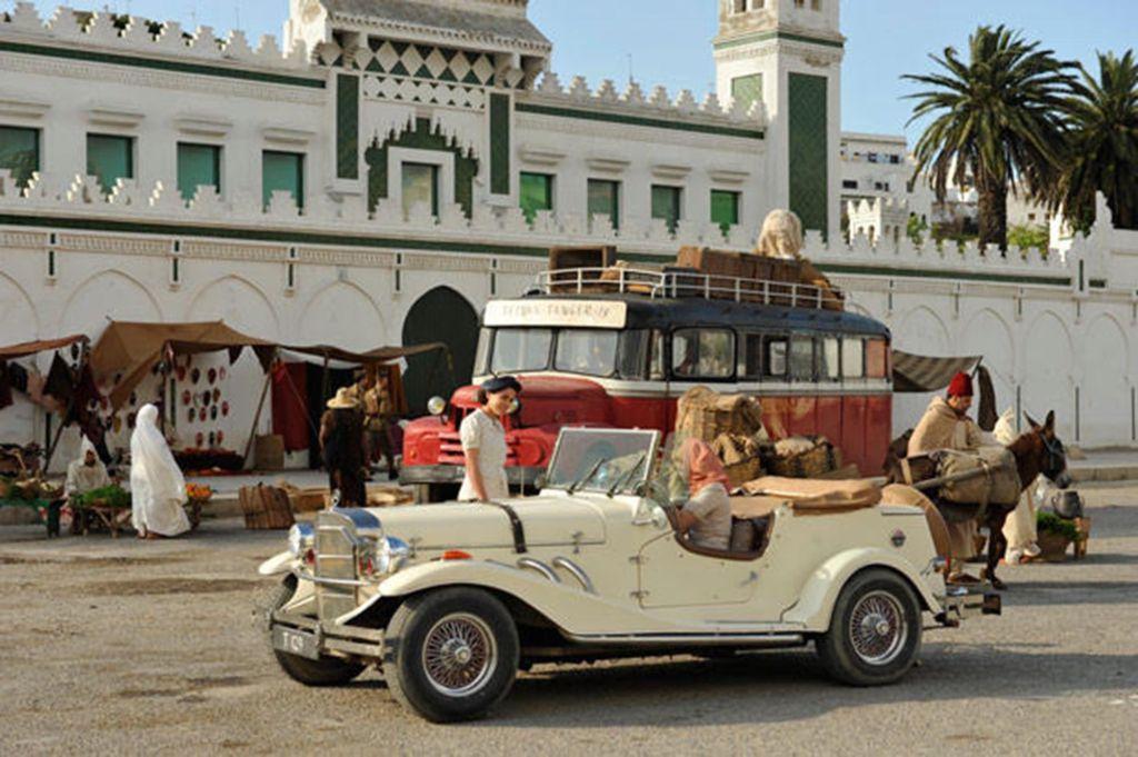 Prédio branco e carros vintage à frente