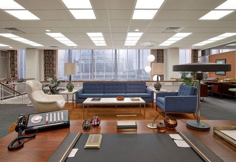 Escritório com sofás azuis, poltrona branca. Janela com persianas ao fundo. Mesa para secretária em madeira