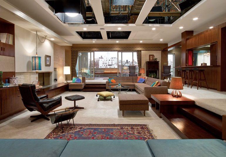 Apartamento com poltronas e sofás. Paredes de madeira. Carpet off-white. Janela ao fundo