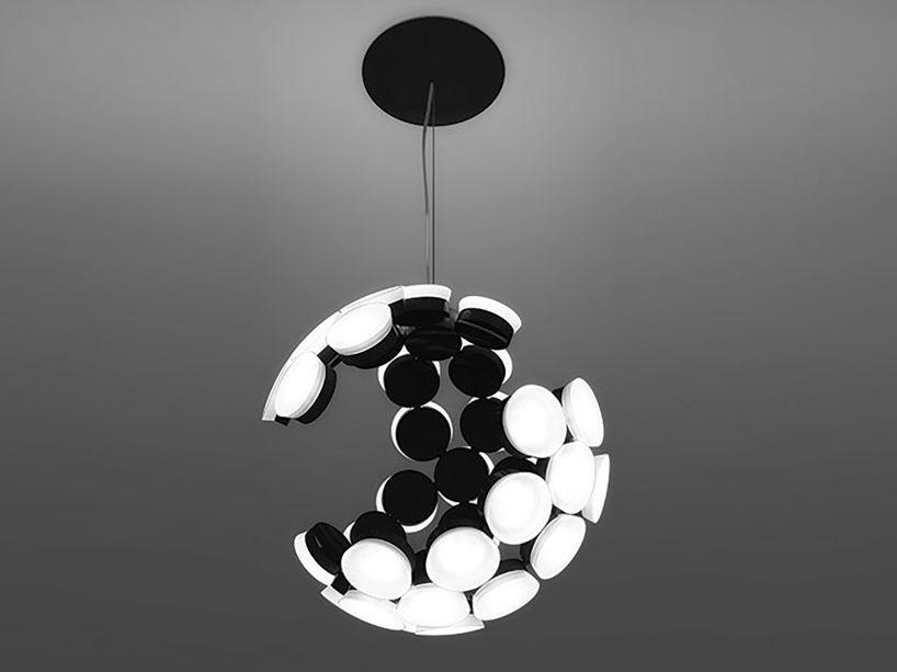 Uma esfera com estrutura incompleta, a luminária suspensa Scopas surpreende por seu design variável, que muda de aparência conforme o ângulo em que é visto. Com design de Neil Poulton, a peça foi criada em alumínio e tecnologia em LED, que dispensa a necessidade de uma lâmpada central — a emissão de luz é feita pela própria placa de design.