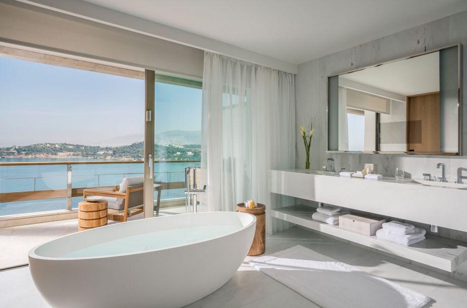 O banheiro segue o design elegante da arquitetura modernista, porém incrementando toques contemporâneos na decoração, como a banheira central, as cores claras e linhas simples que valorizam a vista. Uma TV de plasma foi inserida no espelho para complementar a imersão.