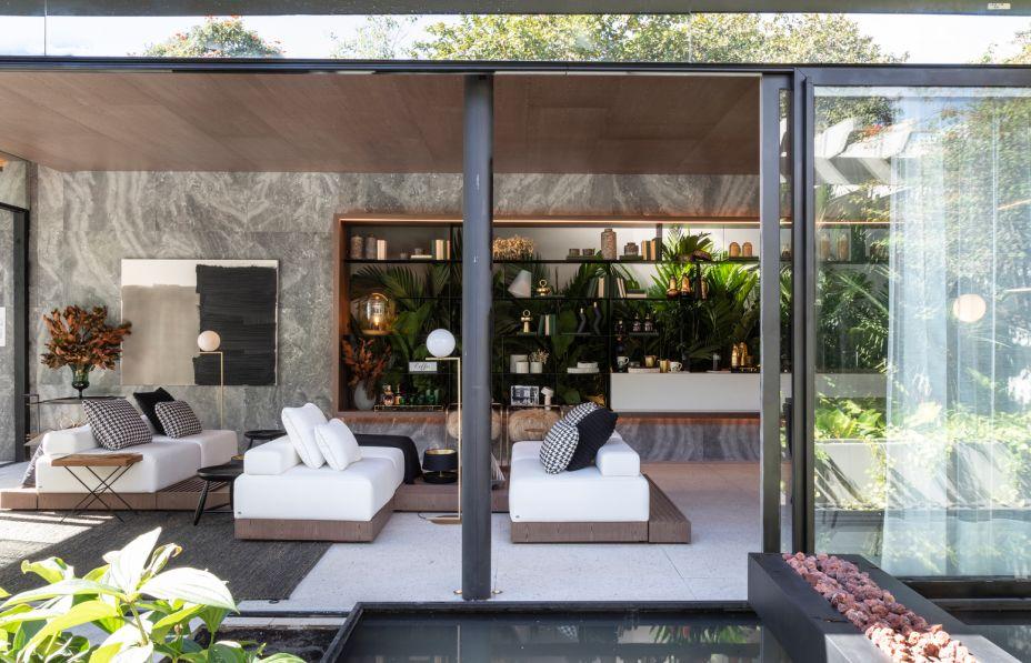 CASACOR São Paulo 2019. Casa Grão por Starbucks at Home - Très Arquitetura. As sócias da Très Arquitetura, guiaram-se pelo conceito do grão, que se define não só pelo nascimento do café, mas pelo princípio de profusas vidas, para desenvolver o ambiente de 100m². Baseadas nas premissas de uma geração que busca por uma vida mais desprendida, altruísta e humanizada, as arquitetas também se inspiraram nas linhas do pavilhão de Mies Van Der Rohe, em Barcelona, e criaram um espaço em formato de caixa de vidro, que engloba living, sala de jantar com uma pequena cozinha, terraço e uma suíte master.