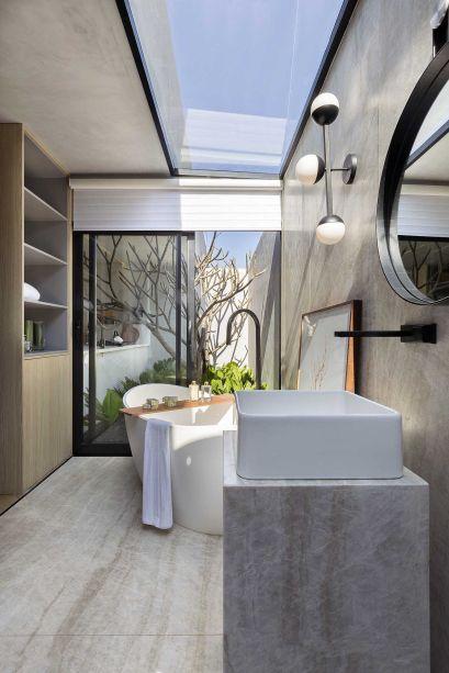 Praticamente não há paredes nem pilares, mas aberturas para a luz e elementos que trazem conexão. Um deles é o painel em pedra rústica que une visualmente a sala de banho.