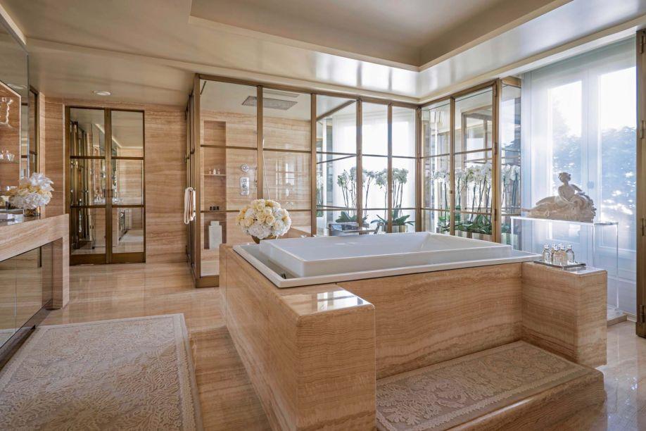 Projetado por Pierre Yves-Rochon, o banheiro tem como ponto focal uma banheira de borda infinita com sistemas de hidromassagem e cromoterapia. A bancada do lavatório recebe a luz de luminárias Baccarat e o revestimento em mármore dá o toque elegante.