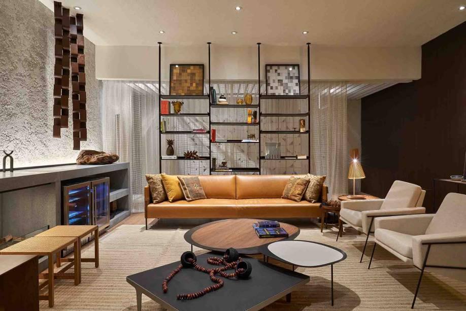Para os espaços integrados, o Living Casapark dá a ideia de delimitar os espaços através de elementos arquitetônicos vazados, como a estante minimalista situada atrás do sofá. A paleta de cores, que vai do marrom, passa pelo verde e o azul, ao cinza, também funciona para unir o apartamento visualmente. Living Casapark - Choque Arquitetura e Design - CASACOR Brasília 2019.