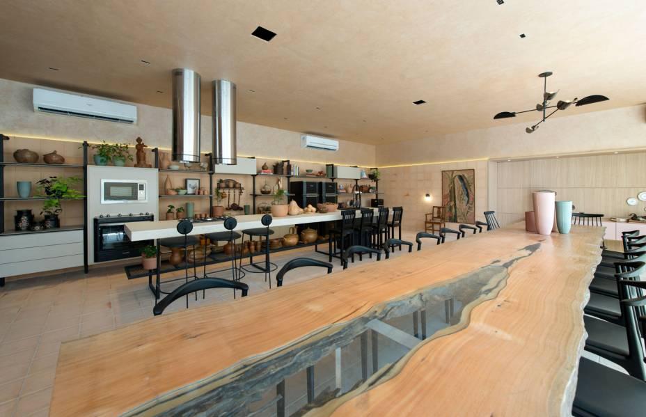 A Cozinha de Origem resgate as cozinhas tradicionais, com o terracota, a cor do barro, adotado no piso, parede e teto, tanto no ladrilho quanto na textura. A mesa de mais de 6 metros de comprimento convida o visitante a se sentar e a compartilhar a experiência com os demais. O único bloco de enormes sofás cria uma sensação de cozinha de estar. Cozinha de Origem - Ana Virginia Furlani - CASACOR Ceará 2019.