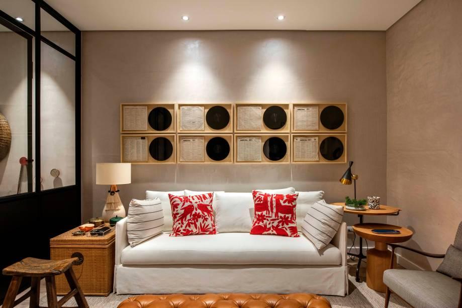 O estúdio de 29m² é aconchegante e explora texturas de materiais naturais como madeira, palha, junco, linho, kilim e couro. Os vinis aparecem emoldurados atrás do sofá confortável, que foram combinados com peças de antiquário e outras modernas, como as luminárias e mesas laterais. Destaque para o rack vermelho, que leva vida ao lugar. Casa de Verdade - Marcela Pepe - CASACOR São Paulo 2019.