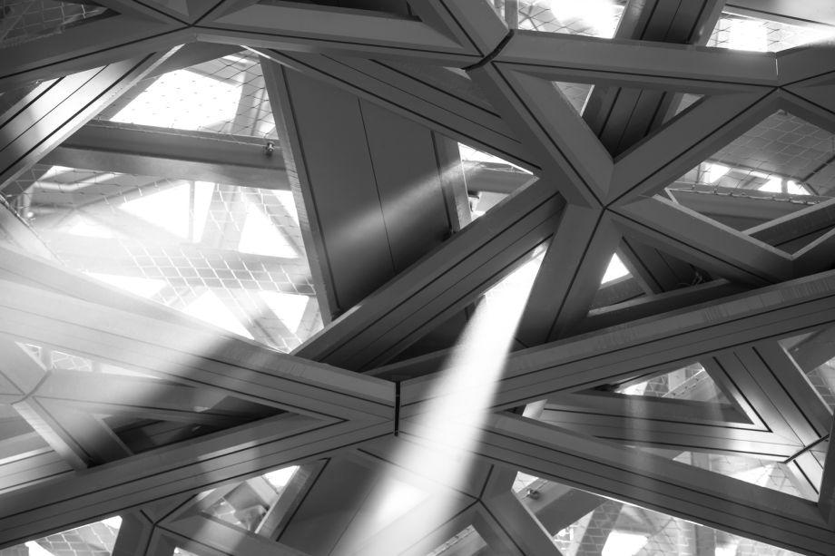 """A cúpula dupla de 180 metros de diâmetro apresenta uma """"geometria horizontal radial e um material têxtil perfurado aleatoriamente, proporcionando sombra pontuada por feixes de sol"""". Construído a partir de 7.850 estrelas metálicas singulares, a estrutura cria uma """"chuva de luz"""" em movimento sob o sol. De acordo com o arquiteto, estas são """"uma reminiscência das folhas de palmeiras sobrepostas dos oásis dos Emirados Árabes Unidos""""."""