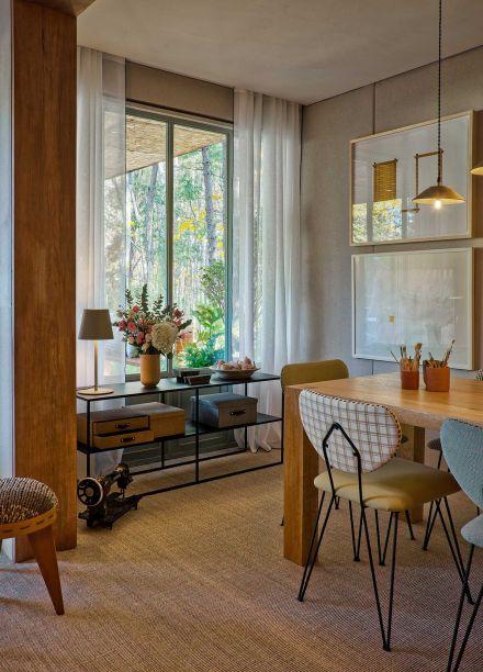 No ateliê, elementos em madeira rústica, estofados estampados e iluminação natural criam uma atmosfera envolvente e aconchegante, característica do estilo vintage.