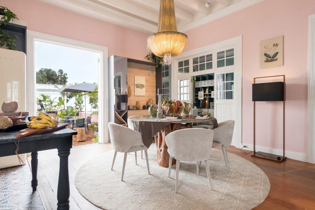 Mesa de jantar com cadeiras brancas sobre tapete circular off white. Lustre coberto de cordas trançadas suspenso