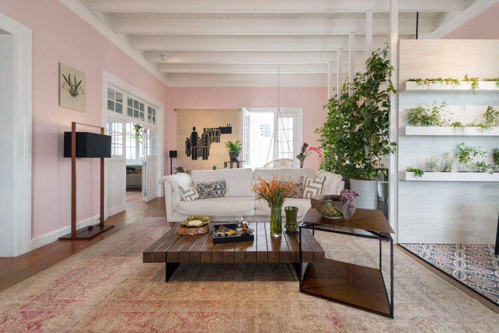 Loft com paredes rosas. Sofá branco no centro com mesa de apoio em madeira