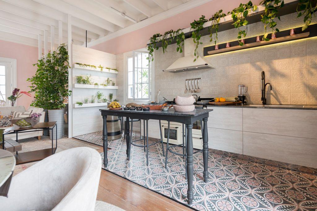 Cozinha aberta com pequena mesa preta no centro. Bancada com pia, fogão e coifa. Plantas na prateleira superior