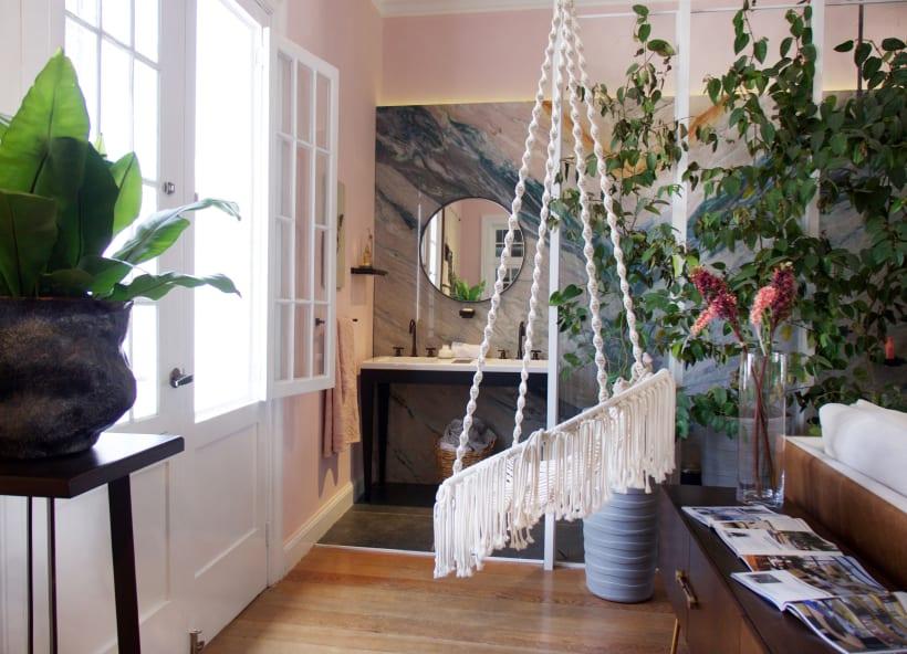 Cadeira balanço em macramê branco voltada para a janela