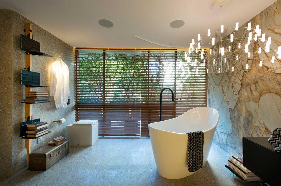 Suíte XX - Anik mourão. CASACOR Ceará 2019. O projeto valoriza os materiais naturais como a pedra e possui uma planta livre, fluida e integrada, com peças clássicas do design. Um luxuoso lustre divide cena com a banheira na área de banho que, junto à quatro estantes minimalistas, compõem um visual elegante.