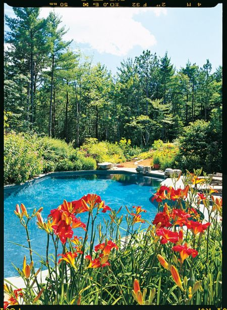 Este extenso complexo do Maine na ilha de Mount Desert é chamado de Rockridge. A piscina da propriedade, rodeada por flores, foi projetada para se parecer com a forma orgânica de um lago. Perto dali, o deck protegido de uma casa com piscina contém cadeiras e sofás de vime para se sentar enquanto aprecia a vista.